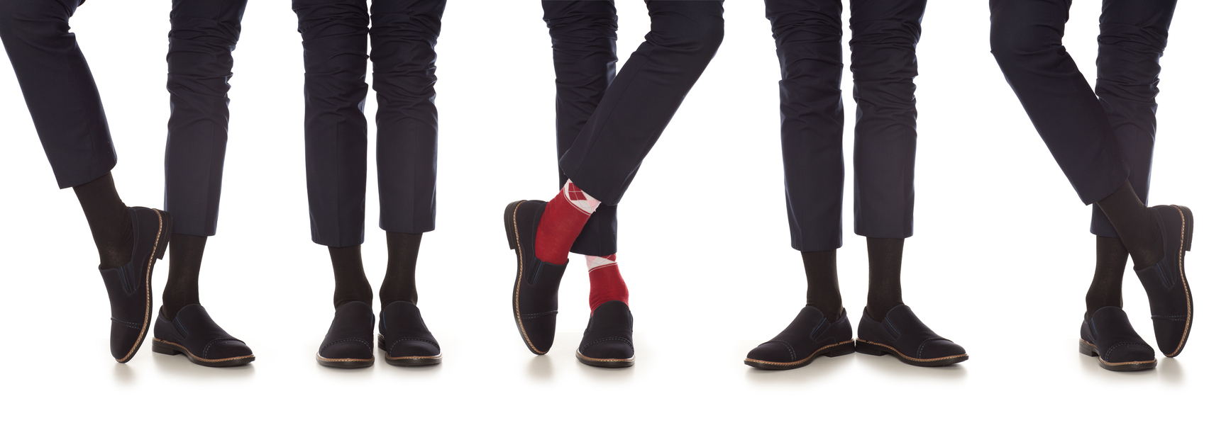 Row of men in black pants and socks except for one  wearing red socks.