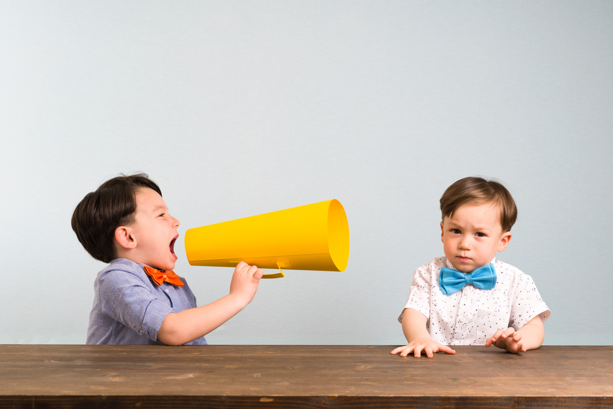 One child yelling through a megaphone at another child.