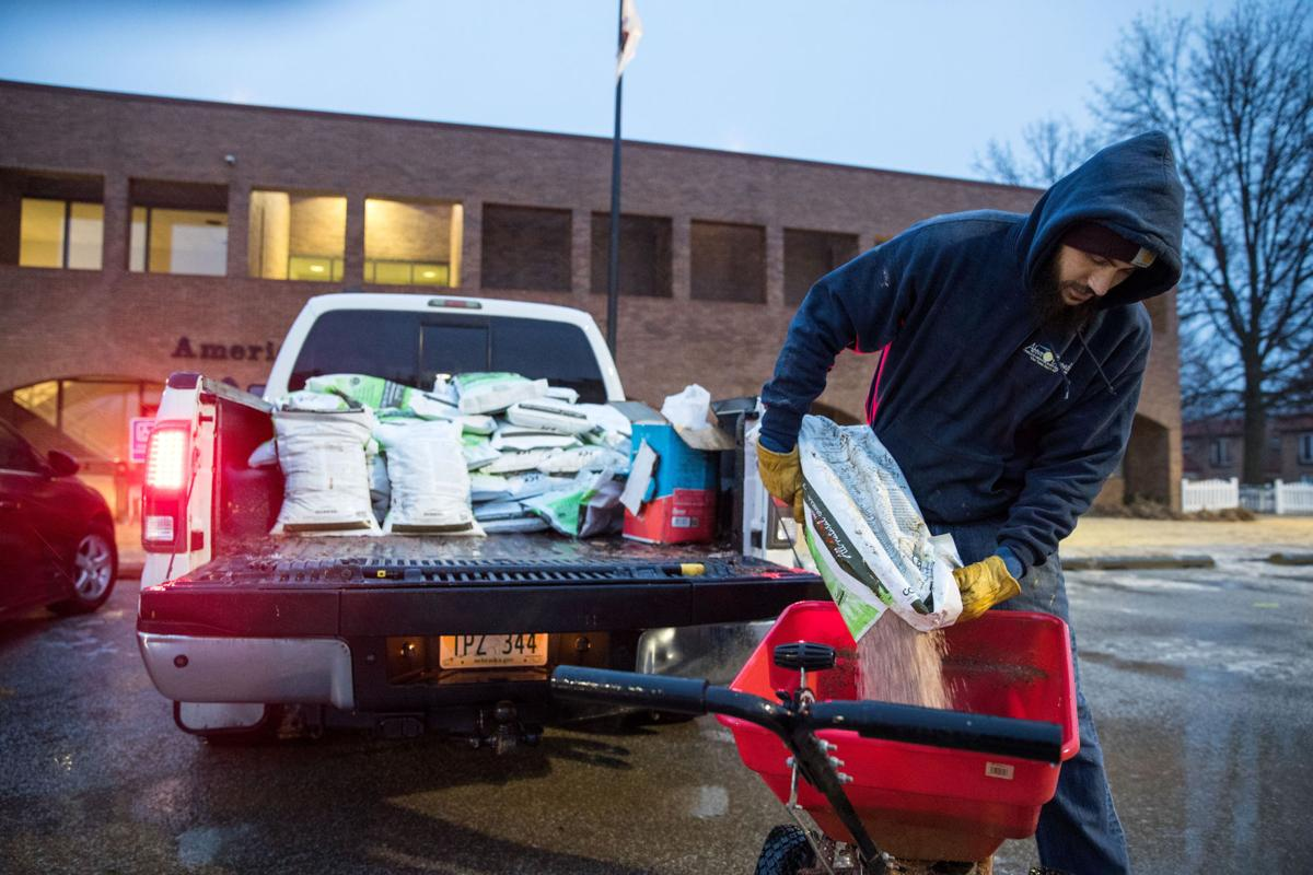 Man pouring ice pretreatment into a wheelbarrow.