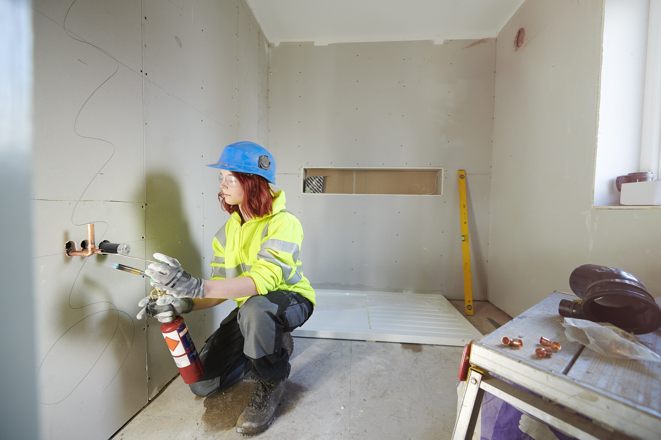 Woman installing plumbing and electrical conduits during renovation.