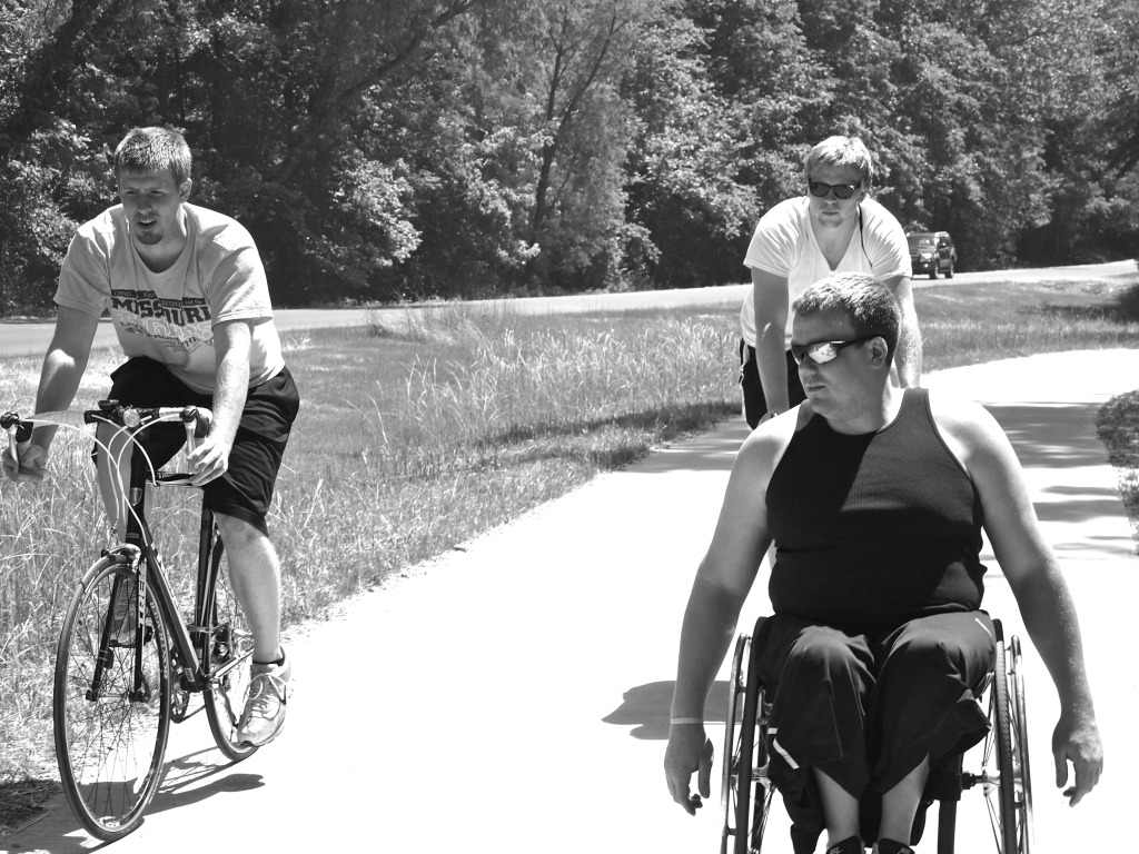 Wheelchair user with two friends on an outdoor trail.
