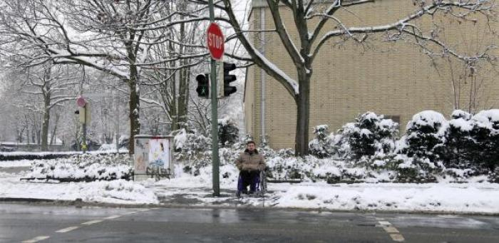 Wheelchair user at front of snowy crosswalk.