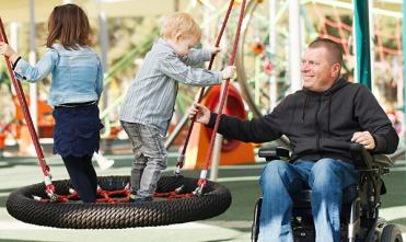 Dad who uses a wheelchair playing with children in an accessible  playground.